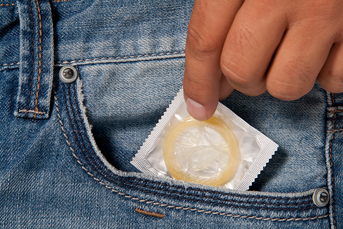 photo of a man pulling a condom from a pocket in a pair of jeans