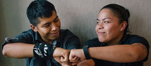 A man and female sitting and smiling with connecting fist pumps. National Latinx AIDS Awareness Day. October 15. Raise awareness about HIV testing and prevention to Latinx communities and provide them with information on access to care.