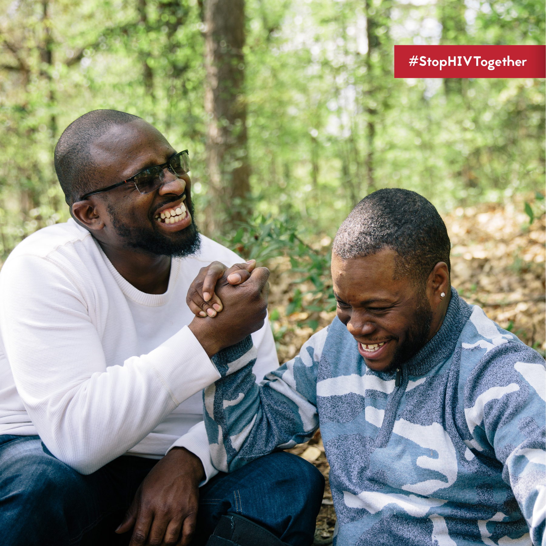 Two men smile while shaking hands in outdoor wooded area. #StopHIVTogether