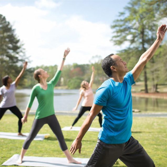 Adults exercise outside on yoga mats near a body of water.