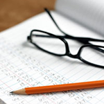 photo of a notebook, glasses and a pencil