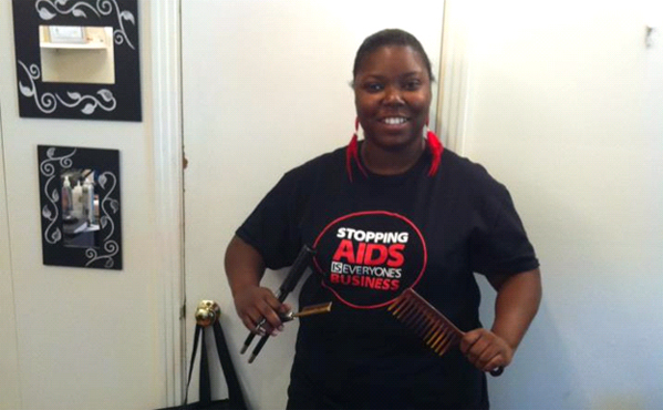 "CDC Hairstylist/Barber HIV Prevention Initiative partner, Jenesta Rogers (Nashville, TN), wears a Stopping AIDS Is Everyone's Business T-shirt to promote ""HIV ShopTalk"" discussions during Divine Interventions Beauty Emporium's  HIV Awareness Day"