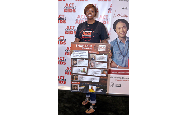Nancy McCreary, hair show volunteer, holds a sign to promote HIV awareness, prevention, and education at the Shop Talk Workshop