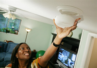 photo of a woman installing a smoke detector