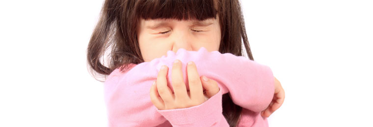 young girl covering her mouth with the bend in her elbow as she sneezes/coughs