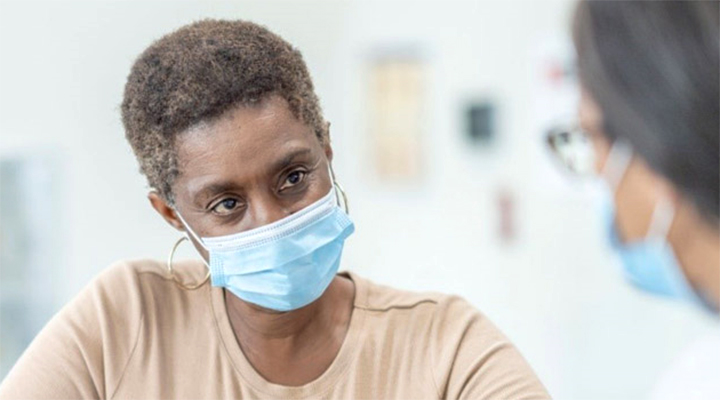 woman wearing mask listening to healthcare provider