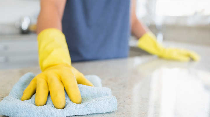 cleaning countertops wearing gloves and cleaning solution