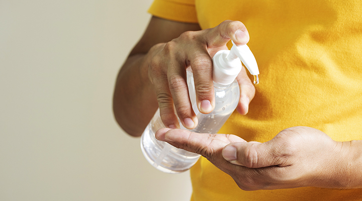 person pumping hand sanitizer into their hand