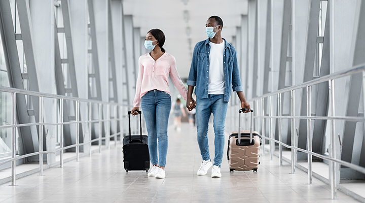 couple wearing masks, holding hands and suitcases in the airport
