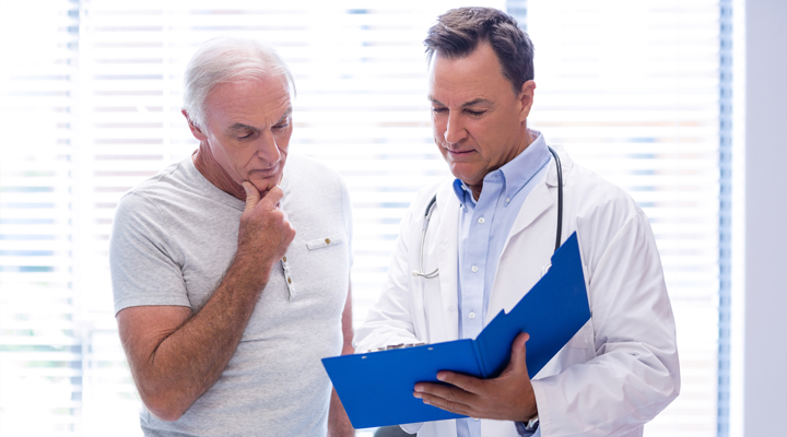 male doctor talking to older adult male patient