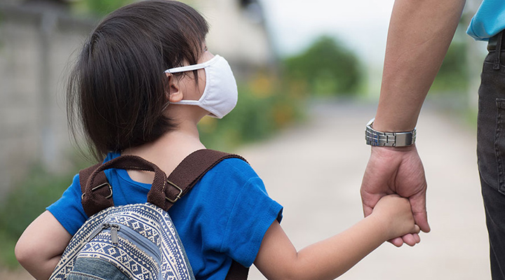 child wearing backpack and mask while holding fathers hand on the way to school