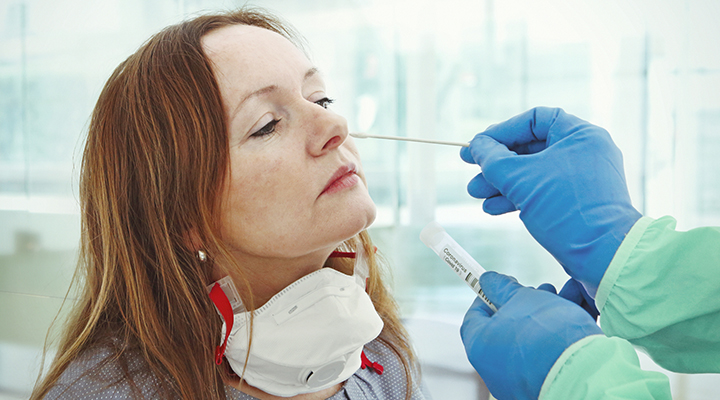 woman getting a nasal swab test from her doctor