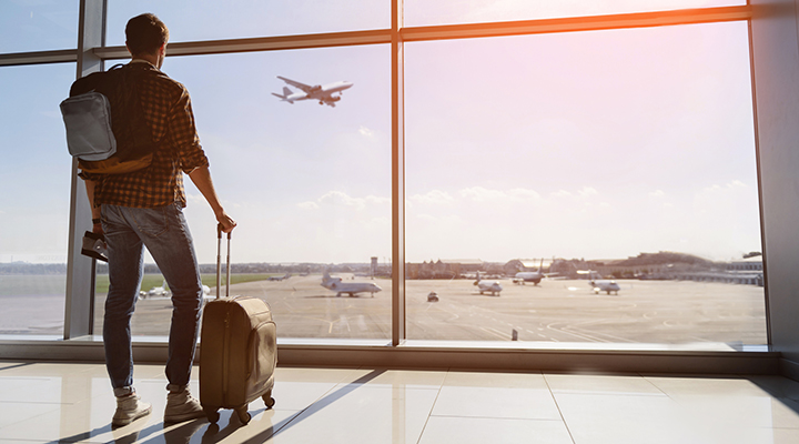 man watching plane take off from inside airport