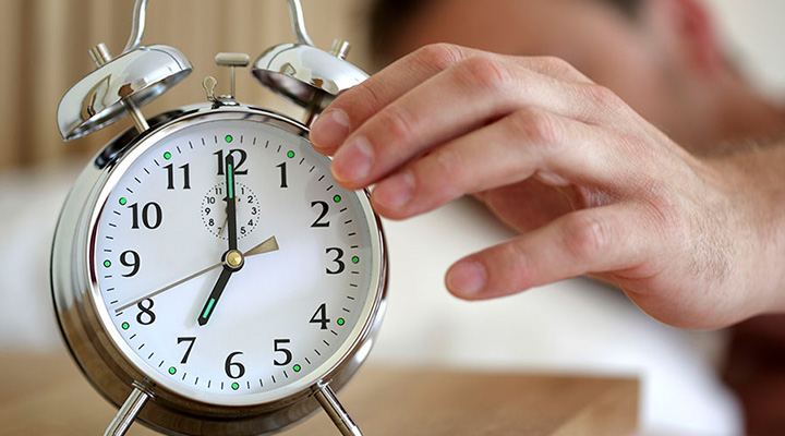 Man's hand reaching for traditional looking alarm clock while in bed.