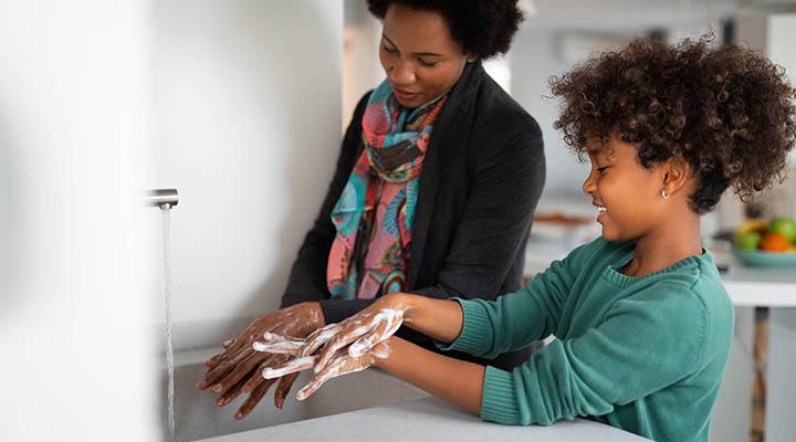 madre e hija lavándose las manos con agua y jabón