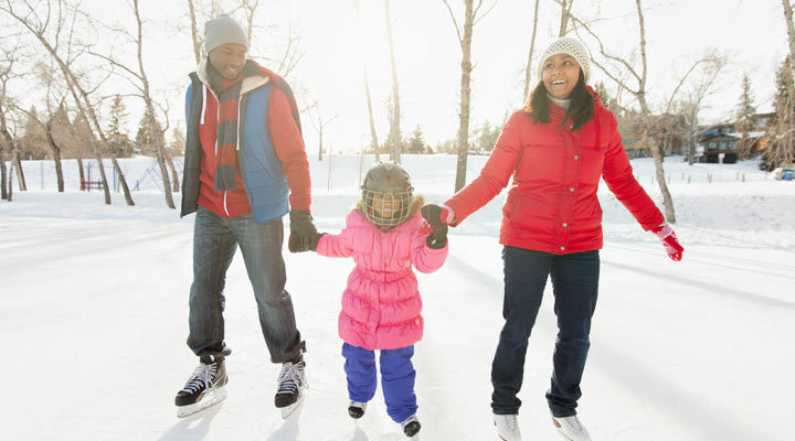 Mom and father ice skating outdoors with young daughter.