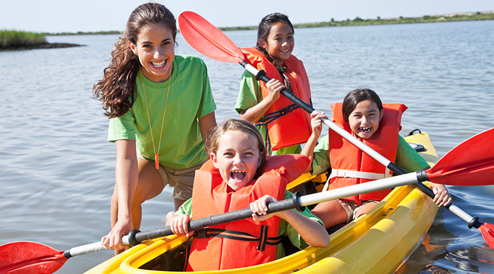 camp counselors helping children in kayak