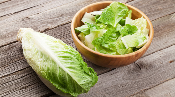 Head of romaine lettuce and a bowl of chopped romaine lettuce