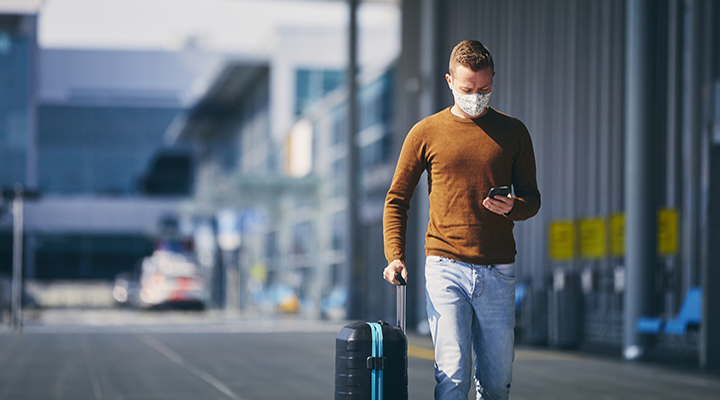 Man wearing face mask and walking to airport terminal