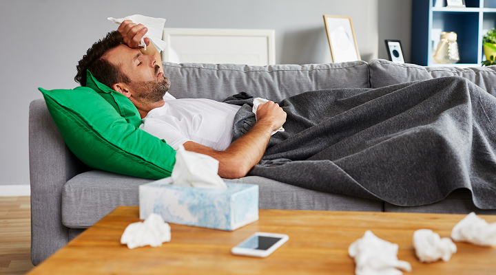 man lying on couch sick