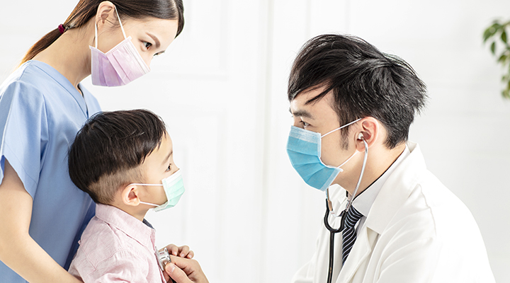 Doctor wearing mask places stethoscope on chest of masked young boy with his masked mother, who stands close to him watching