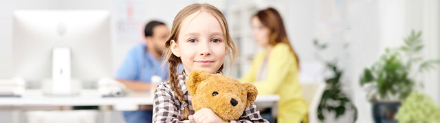 Child holding her teddy bear with parent talking to doctor in background