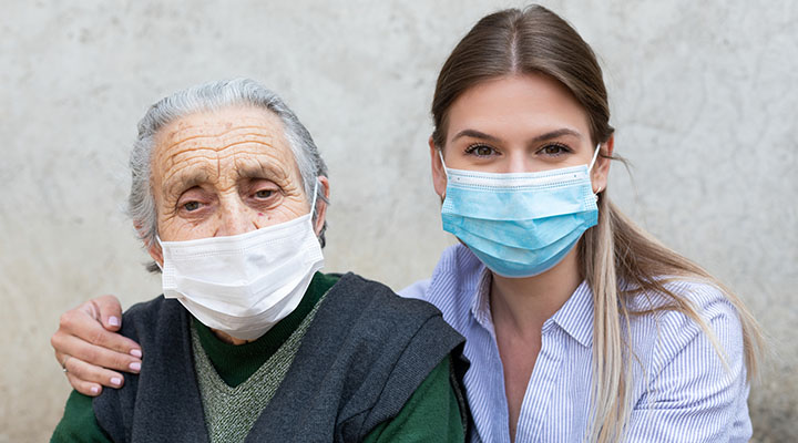 elderly woman and caregiver wearing masks