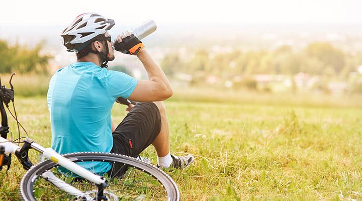 man wearing helmet taking a break from a bike ride drink water