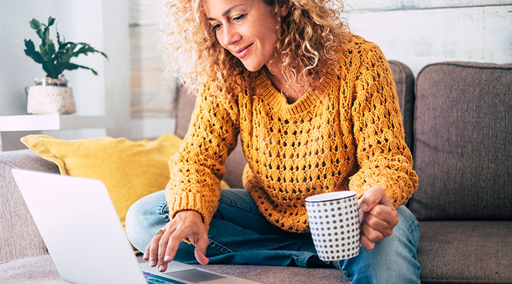woman at home on computer with coffee
