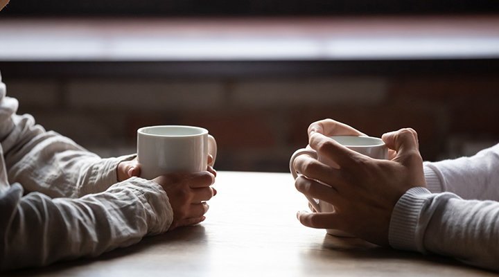 hands holding coffee over table