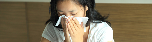 Woman sick in bed wiping her nose