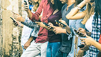 Multiple people checking mobile devices