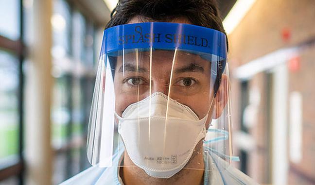 hombre con una mascarilla y unprotector facial de plástico