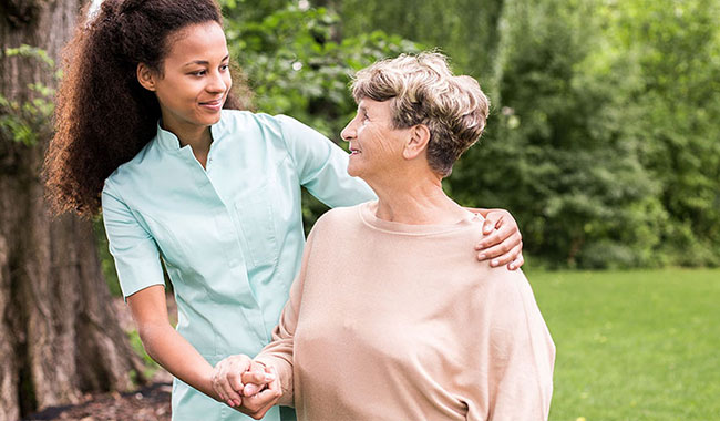 A young health care worker helping an older woman steady herself