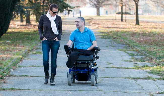 Woman walking besides man in wheelchair
