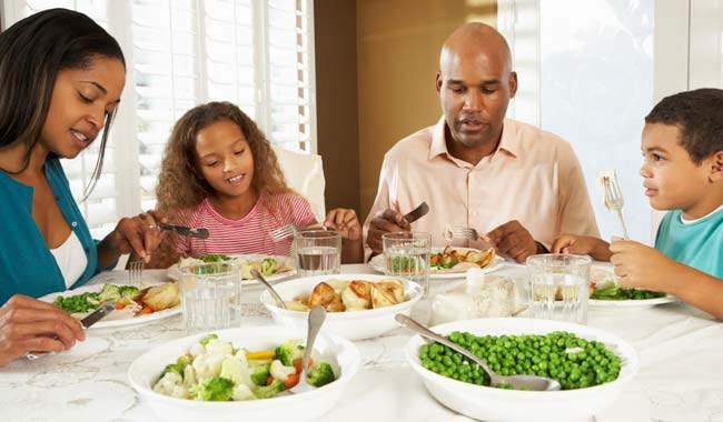Family of four eating a meal at the table