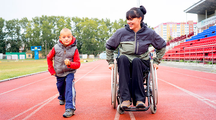 Child running next to woman in wheelchair on track
