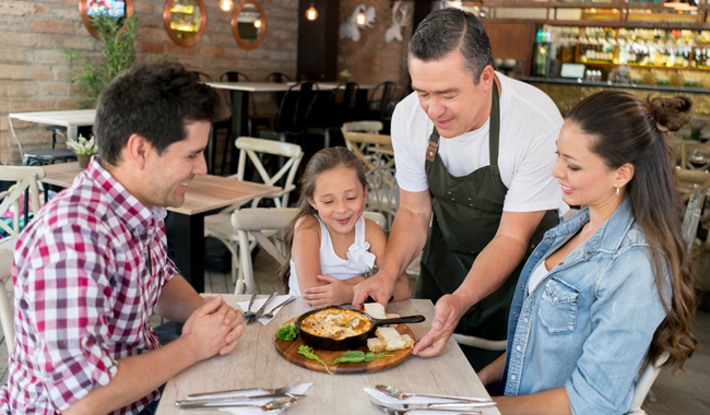 Server placing entrée at a table for a family of three