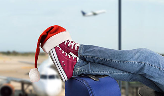 Person's feet on suitcase with santa hat on sneakers