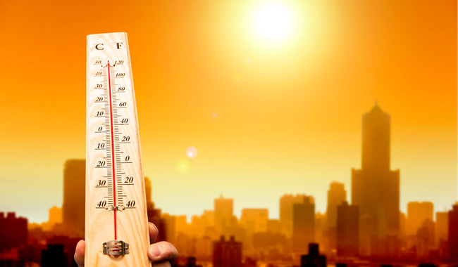 thermometer held up over sunny cityscape