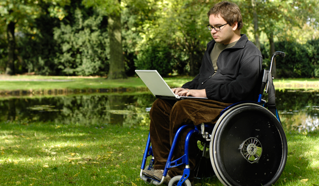 Man in wheelchair using laptop