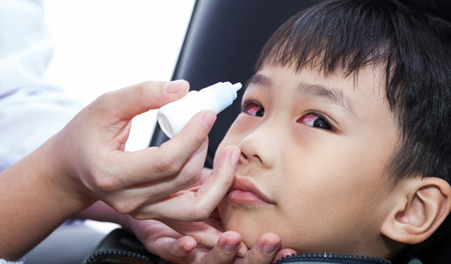 Young boy with irritated eyes receiving eye drops