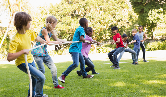 Image of preteen children playing tug-a-war