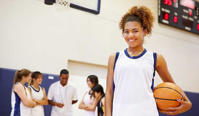 Teenage girl in school gym with basketball