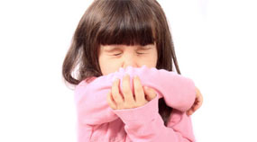 Young child sneezing into sleeve