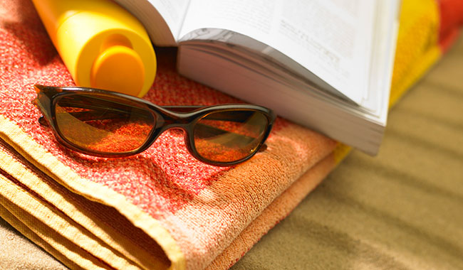 Sunglasses, sunscreen, book and beach towel