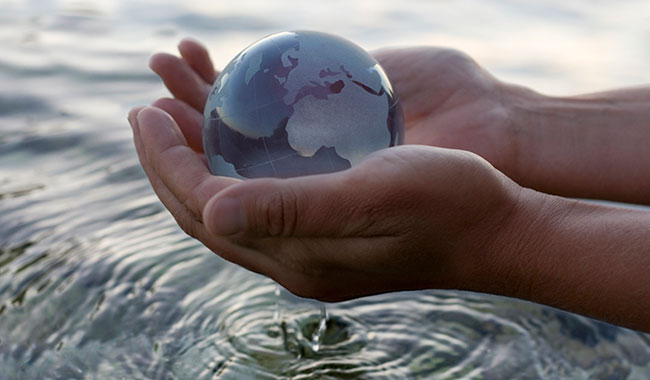Image of hands holding glass globe over water