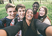 group of male and female teenagers smiling taking a photo