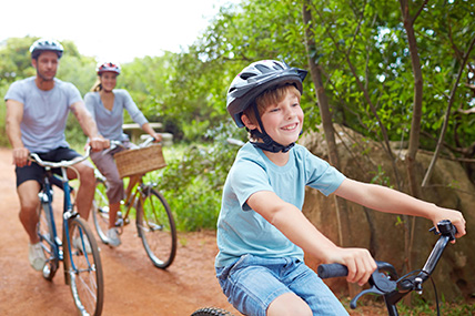 Young couple riding bikes with son