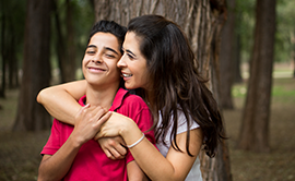Teen couple hugging and smiling